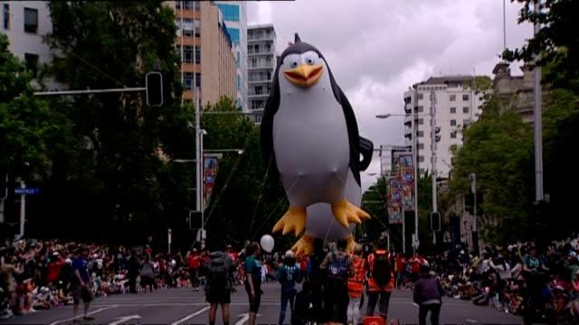 vidéos et rushes de giant helium penguin balloons and circus float at annual farmers santa parade along queen street in auckland - char de défilé
