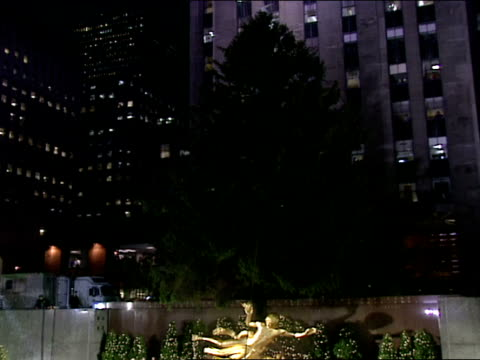 giant norway spruce behind prometheus statue at edge of ice skating rink. - illuminazione dell'albero di natale del rockefeller center video stock e b–roll