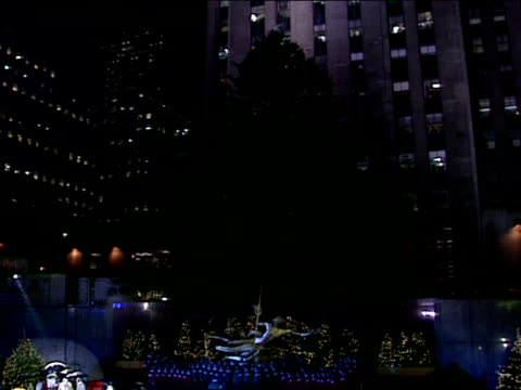 giant norway spruce behind prometheus statue at edge of ice skating rink in rockefeller plaza lights on tree - クリスマスツリー点灯式点の映像素材/bロール