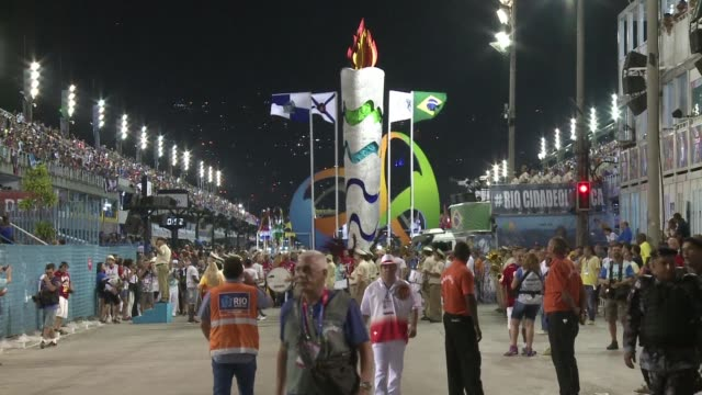 A giant Olympic torch on a float opened Rio Carnivals prestigious main parade Sunday night as the city prepares to host the global sporting event...