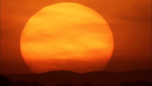 A giant orange sun sets behind silhouettes of low desert hills in Shibam.