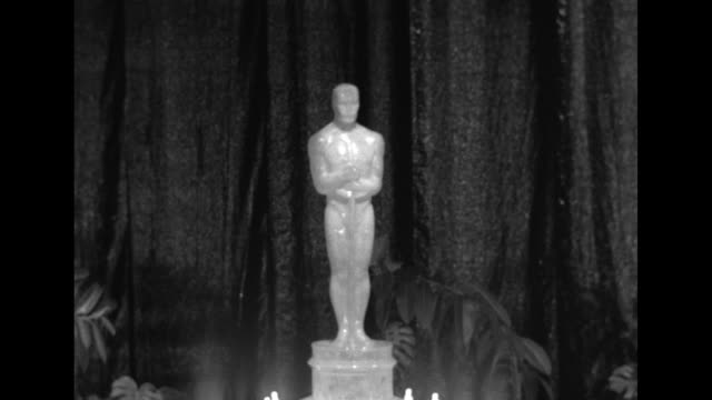 MS giant Oscar statue tops a birthday cake display at the Pantages Theatre in Los Angeles pan down actor Ronald Colman reads a list of nominees for...