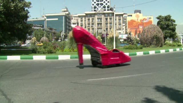 vídeos y material grabado en eventos de stock de a giant racy red motorised stiletto is not what you expect to see cruising down the avenues of iran's capital but it certainly attracts attention and... - cruising
