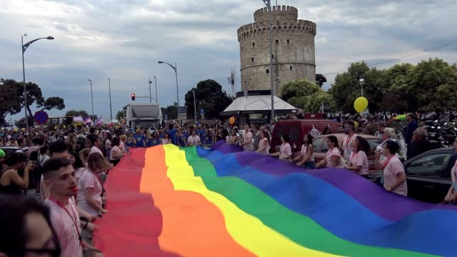 a giant rainbow flag is waving ahead of the white tower of thessaloniki while is being carried by activists during the pride parade more than 13000... - intersex stock videos and b-roll footage