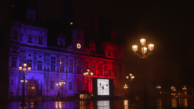 vidéos et rushes de giant screen with photos of jacques chirac in front of the city hall of paris. a man with an umbrella walks on the square on september 27, 2019.... - mairie