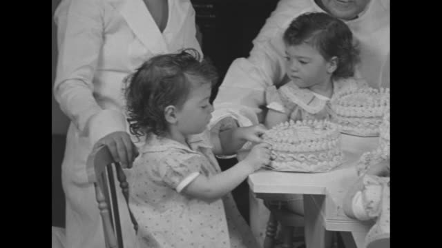 giant second birthday card for dionne quintuplets / 2 nurses dressing and combing hair of cecile and marie dionne / nurse brings cake to table with... - ontario canada stock videos & royalty-free footage