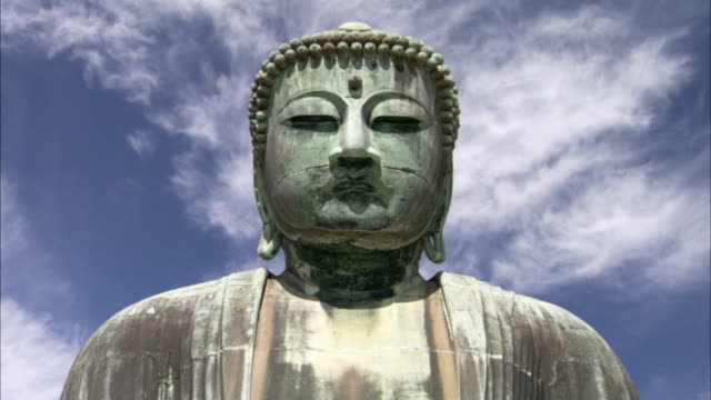 a giant, serene buddha statue contrasts against a blue sky streaked with clouds. - statue stock videos & royalty-free footage