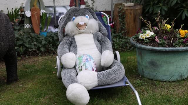 vídeos de stock, filmes e b-roll de giant soft bunny lies on a sun lounger with an easter egg in his lap in a garden outside an apartment building in district zehlendorf on easter... - suavidade