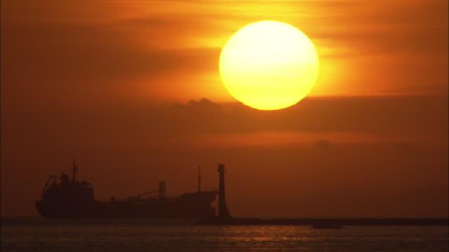 vídeos y material grabado en eventos de stock de a giant sun glows above a silhouetted ship on manila bay. - vista marina