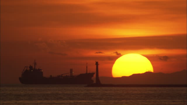 A giant sun sinks below the horizon near a silhouetted ship on Manila Bay.