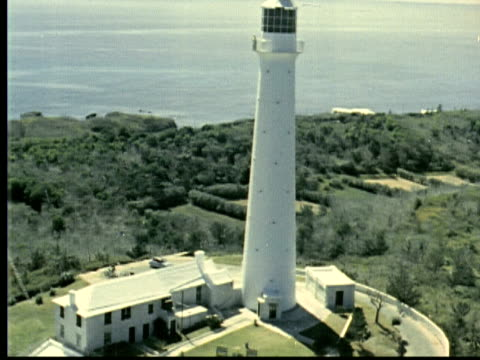 stockvideo's en b-roll-footage met 1963 montage gibbs hill lighthouse. couple on top, woman's hat blows off and falls though air / bermuda - sociale geschiedenis