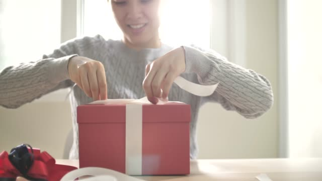 gift wrapping, woman tie a white ribbon bow for chirstmas event - birthday gift stock videos & royalty-free footage
