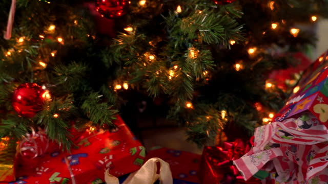 gifts sit under a christmas tree. - christmas tree stock videos & royalty-free footage