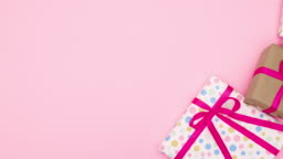 Gifts with pink ribbons appear on right side of pink theme. Stop motion