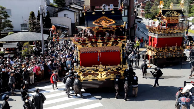 """gifu prefecture--a """"karakuri"""" mechanical doll is perched precariously on what resembles a diving board jutting from the top of a towering parade... - ドール点の映像素材/bロール"""