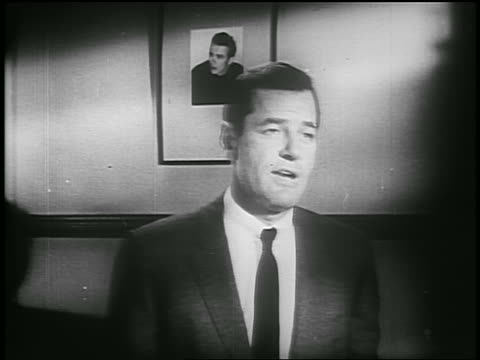 gig young talking to someone off screen / photo of james dean on wall in background / psa - solo uomini di età media video stock e b–roll