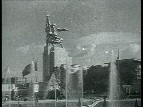 stockvideo's en b-roll-footage met gigantic statue of worker and kolkhoz woman by vera mukhina in front of soviet pavilion in paris exposition people entering soviet pavilion / paris... - 1937