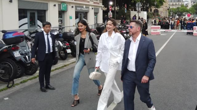 gigi hadid wears a brown cap earrings necklaces a white shirt with cartoon drawings pattern assorted flare pants outside vuitton during paris fashion... - fashion industry stock videos & royalty-free footage