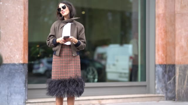 gilda ambrosio wears a checkered skirt with black fur red fur shoes a checkered jacket a white top and uses a smartphone outside moncler during paris... - skirt stock videos & royalty-free footage