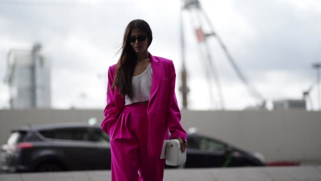 Gilda Ambrosio wears sunglasses a white top a neon pink pantsuit a white bag black pumps outside Giambattista Valli during Paris Fashion Week...