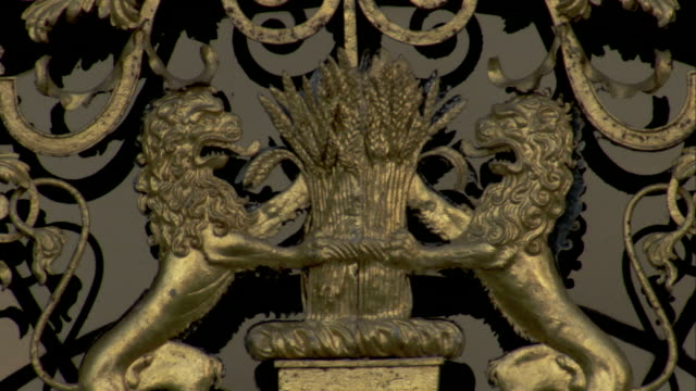 vídeos y material grabado en eventos de stock de gilded metalwork depicts two lions around a bundle of wheat, burghley house, northamptonshire. available in hd. - northamptonshire