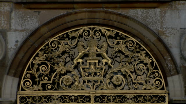 vídeos y material grabado en eventos de stock de gilded metalwork depicts two lions in an elaborate pattern, burghley house, northamptonshire. available in hd. - northamptonshire