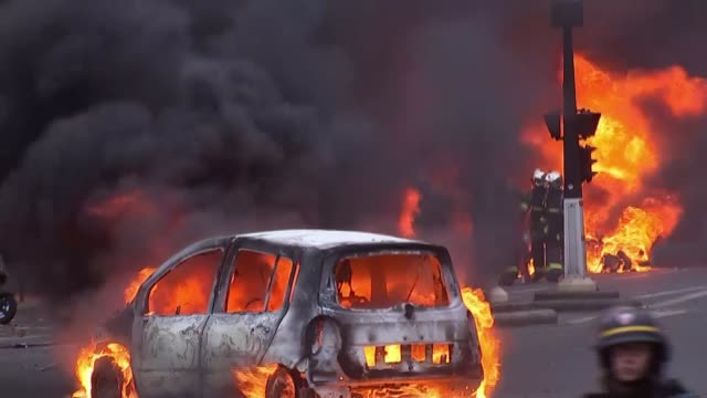 over a thousand arrested as riots continue FRANCE Paris EXT Various shots cars burning in street Various of riot police along street towards burning...