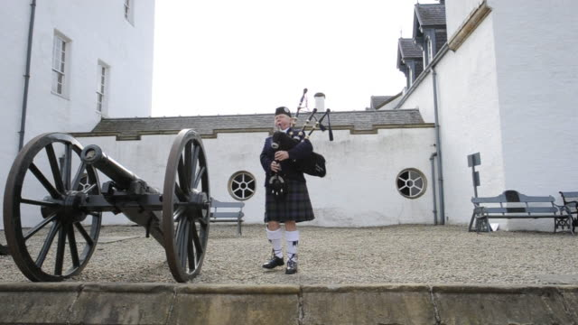 gillie mcnab plays her bagpipe beside a cannon at blair castle. - perthshire stock videos & royalty-free footage