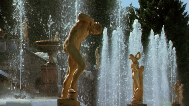 Gilt statues stand in a Peterhof fountain.