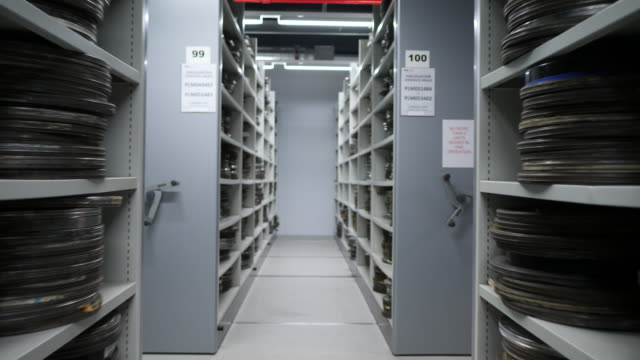Gimbal shot moving through a vault containing shelves with film cans