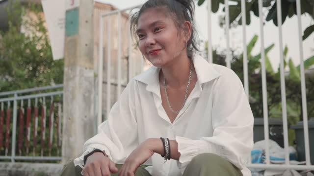 vídeos y material grabado en eventos de stock de gimbal shot : retrato feliz mujer asiática bronceada piel con surfskate en la calle. - equilibrio vida trabajo