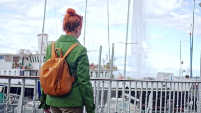 湖のほとりを歩いて生姜女性 - 赤毛点の映像素材/bロール