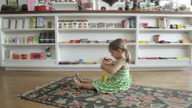 WS Girl 2-3 sitting and eating candies in candy stores / Minneapolis, Minnesota, USA