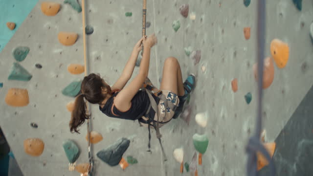 girl abseiling off a wall in an indoor climbing gym,slow motion - abseiling stock videos & royalty-free footage