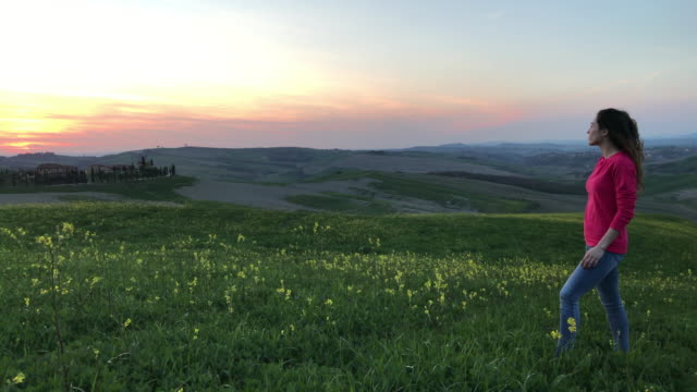 vídeos y material grabado en eventos de stock de a girl admires the sunset near a farm in asciano. baccoleno, asciano, val d'orcia, siena - rosa brillante