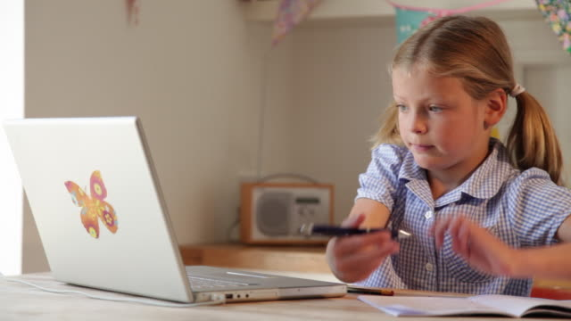 girl aged 8 years using laptop for homework at kitchen table close up. static - inghilterra video stock e b–roll
