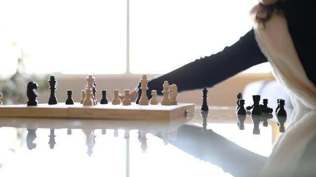 動きを作るためにチェスボードを分析する女の子 - dia点の映像素材/bロール