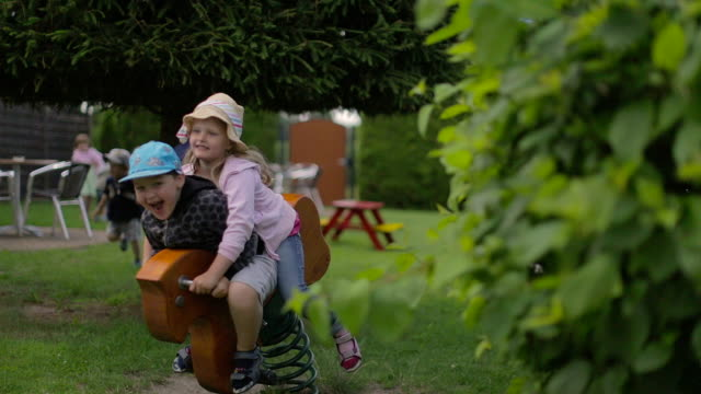 A girl and a boy riding together on a rocking horse