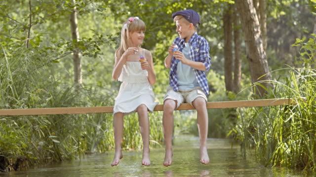 DS-Mädchen und der junge sitzt auf den creek und blowing bubbles