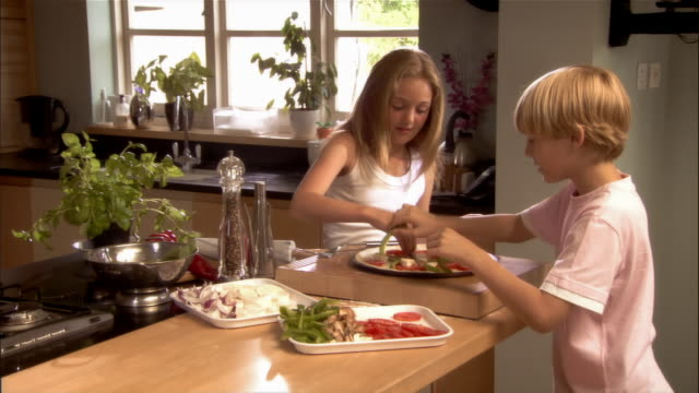 Girl and boy adding vegetable toppings to pizza on kitchen counter