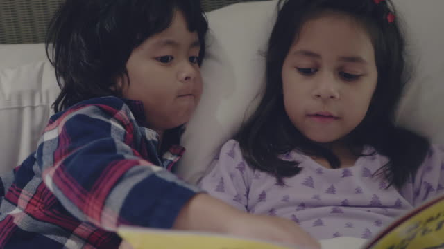 girl and boy are reading book on the bed at home - bedtime stock videos & royalty-free footage