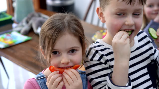 girl and boy covering mouth with slice of pepper - children only stock videos & royalty-free footage