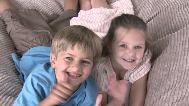 vídeos y material grabado en eventos de stock de girl and boy jumping onto beanbag and waving at camera - saludar con la mano