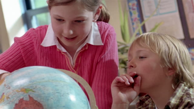 stockvideo's en b-roll-footage met girl and boy looking at globe / gorham, maine - bureauglobe
