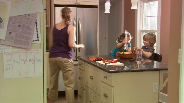 ms girl and boy mixing salad in kitchen while mother brings over glass of water / westfield, new jersey, usa - fleischzange stock-videos und b-roll-filmmaterial