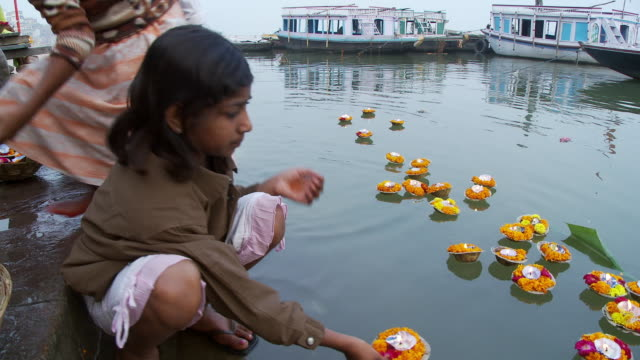 Girl and boy placing floating candles in water and pushing them away from shore