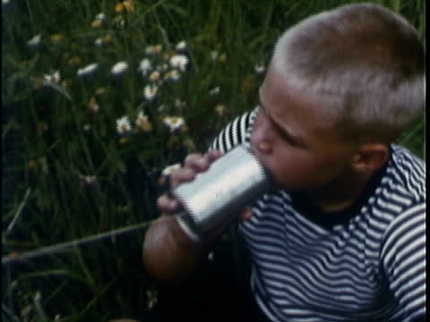 1969 MONTAGE Girl and boy playing can phone in meadow / USA