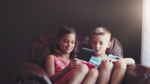 girl and boy playing game on digital tablet - focus on background stock videos & royalty-free footage