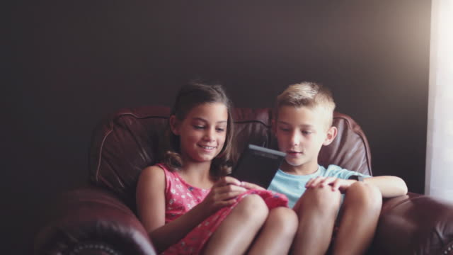 girl and boy playing game on digital tablet - 前ボケ点の映像素材/bロール