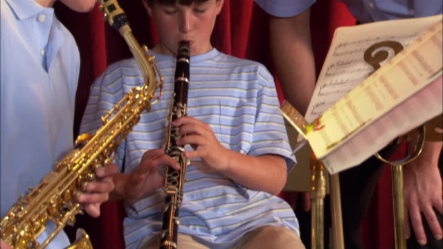 stockvideo's en b-roll-footage met girl and boy playing instruments during band practice / music teacher coming over and instructing children / los angeles, california - oefenen